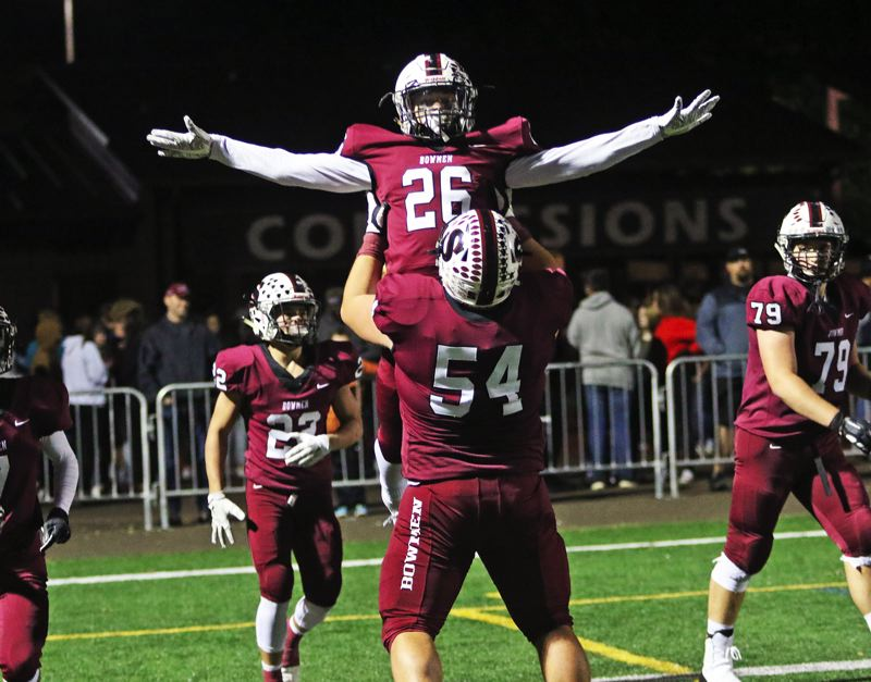 PMG PHOTO: DAN BROOD - Sherwood High School senior Brody Stevens (26) celebrates with senior lineman Nick Severson following his 60-yard touchdown run in the Bowmen's 42-10 win over McMinnville.