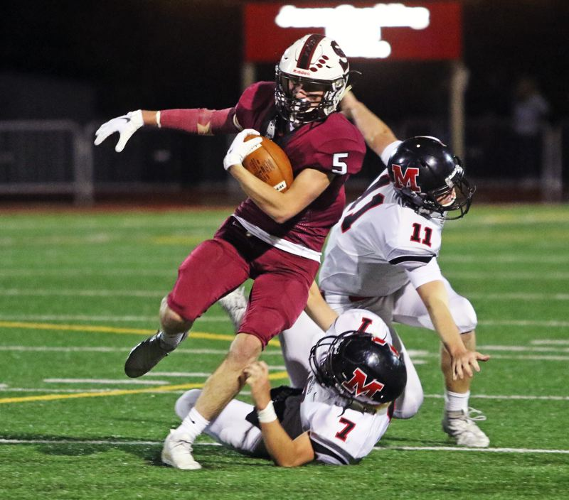 PMG PHOTO: DAN BROOD - Sherwood High School junior Jackson Hannan looks for yardage on a punt return during the Bowmen's 42-10 win over McMinnville on Thursday.