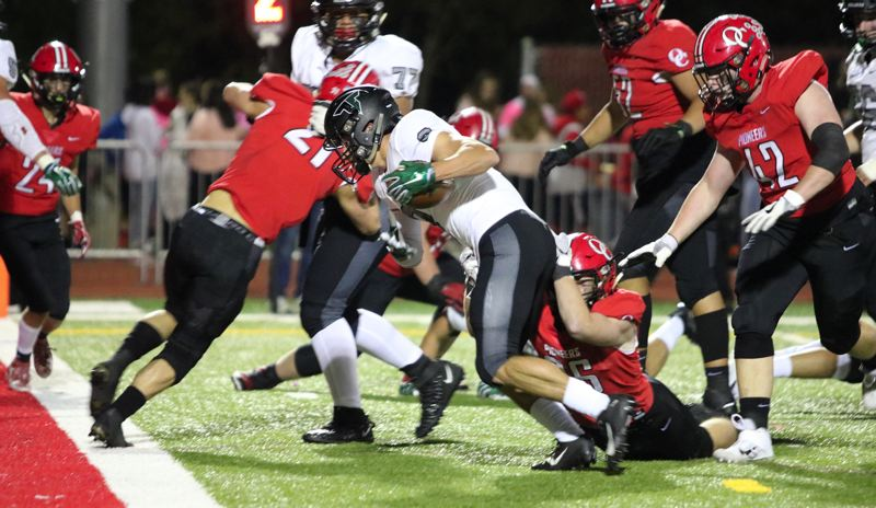 PMG PHOTO: JIM BESEDA - Tigard running back Hunter Gilbert (with ball) drags Oregon City linebacker Zac Woods (26) with him as he lunges for the goal line and the first of his two touchdown runs in Friday's 50-13 win.