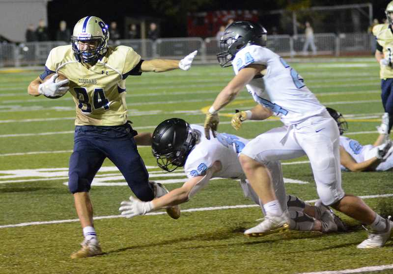 PMG PHOTO: DEREK WILEY - Canby junior Chance Miller runs away from a couple of Lakeridge defenders Friday night.
