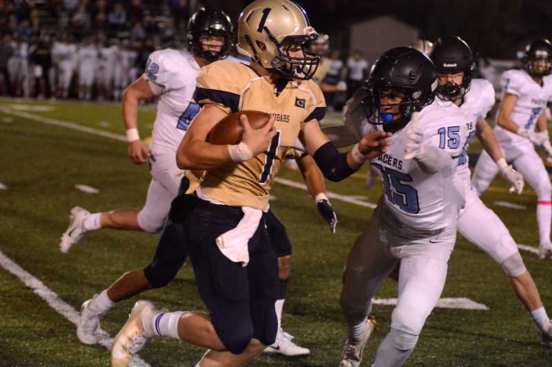 PMG PHOTO: DEREK WILEY - Canby quarterback Mikey Gibson runs the ball against Lakeridge Friday.