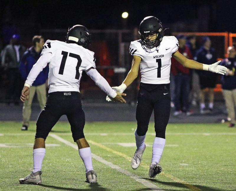 PMG PHOTO: DAN BROOD - Tualatin High School senior quarterback Blake Jackson (17) and senior receiver Cade McCarty congratulate each other after teamming up for a pass completion in the Wolves' 42-14 win at Westview.