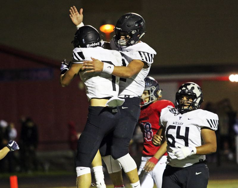 PMG PHOTO: DAN BROOD - Tualatin High School seniors Luke Marion (left) and John Miller celebrate following one of Marion's three touchdowns in the Wolves' 42-14 win over Westview.