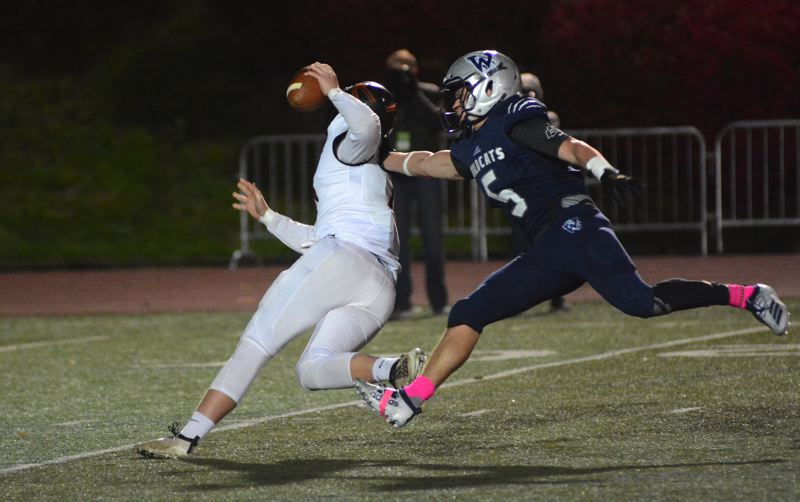 PMG PHOTO: DEREK WILEY - Wilsonville junior Chad Overholt pressures Scappoose quarterback Luke McNabb.