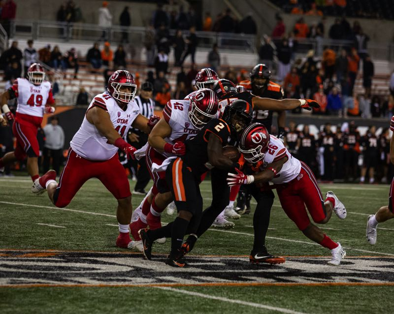 COURTESY PHOTO: MEGAN CONNELLY - Utah's defense swarms Calvin Tyler Jr. of Oregon State during Saturday night's game at Reser Stadium.