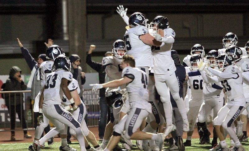 PMG PHOTO: MILES VANCE - Lake Oswego's players leap for joy after they beat West Linn 20-17 on the final play of their Friday, Oct. 11, contest at West Linn High School.