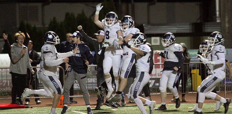 PMG PHOTO: MILES VANCE - Lake Oswego senior running back Casey Filkins (center, no. 9) leaps into the air after scoring a touchdown on the final play of the game to beat West Linn 20-17 at West Linn High School on Friday, Oct. 11.