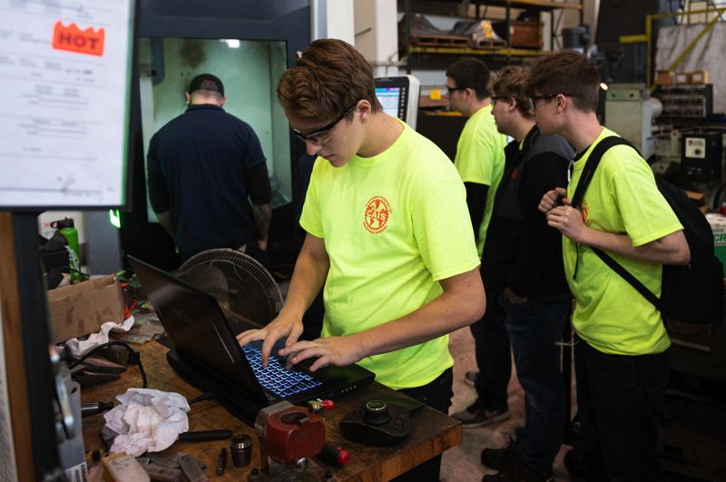 PAMPLIN MEDIA GROUP: CHRIS OERTELL - Clackamas Academy of Industrial Science student Eryck Stratton uses a computer to enter his name for a name tag that will be created on a CNC mill during a manufacturing day event at American Machine & Gear in Northwest Portland, on Friday, Oct. 4. The event is to expose students to the world of manufacturing.