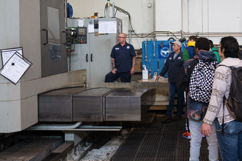 PAMPLIN MEDIA GROUP: CHRIS OERTELL - Norman Besand (facing camera, right), superintendent at American Machine & Gear in Northwest Portland, shows 12th graders around on Manufacturing Day, Oct 4. Besand hopes that some of the students from the Open School will get a taste for machine shop work and come back and work there one day. Students are checking out a horizontal CNC boring mill that is cutting holes in a worm gear.