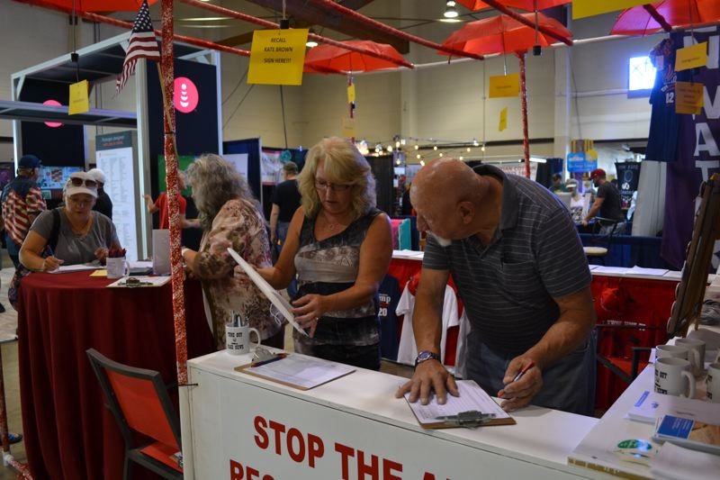 PMG FILE PHOTO - Volunteers at the Marion County GOP booth at the Oregon State Fair help people sign petitions to recall Gov. Kate Brown.,
