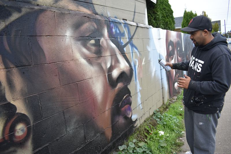 PMG PHOTO: SHANNON O. WELLS - Rockwood resident Mario DeLeon adds finishing touches to his drawing of the late Nipsey Hussle, who joins other rap and comics characters on a wall in his neighborhood along 181st Avenue.
