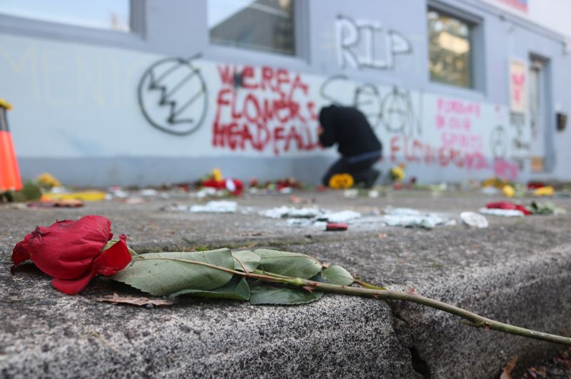 PMG PHOTO: ZANE SPARLING - A man pays his respects at a memorial for Sean Kealiher's outside the Democratic Party of Oregon offices in Northeast Portland.