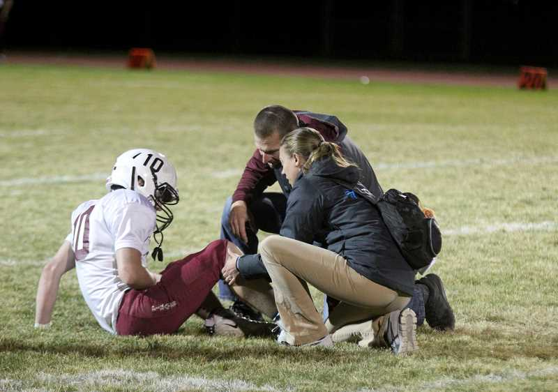 STEELE HAUGEN - Madras High School athletic trainer Nicole Porter tends to an injured Dayton football player during a football game Sept. 27.