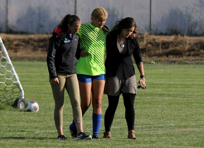 STEELE HAUGEN - Athletic trainer Nicole Porter helps Madras girls soccer goalie Cheydon Herkshan off the field because of a knee injury.