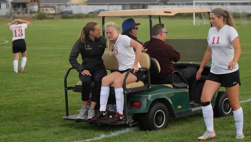 STEELE HAUGEN - An injured soccer player gets carted off the field with athletic trainer Nicole Porter evaluating her injury.