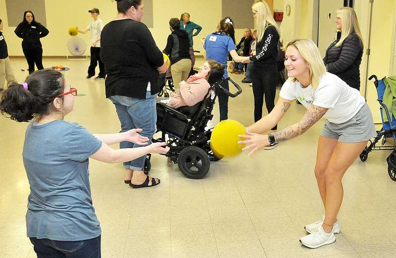 GRAPHIC PHOTO: GARY ALLEN - Alexis Hayes plays ball with a participant in the T.H.R.I.V.E. fitness class in the youth building at the Chehalem Armory Center last week.