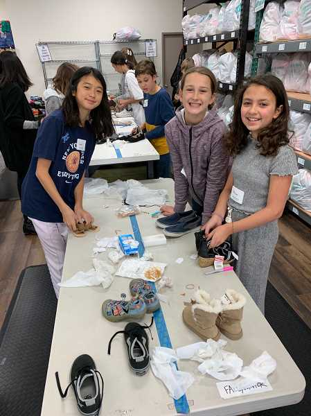 COURTESY PHOTO - Lake Oswego Junior High students Grace Peng, Ava Beach and Isabel Alles volunteering at With Love, a non-profit that supports foster families.
