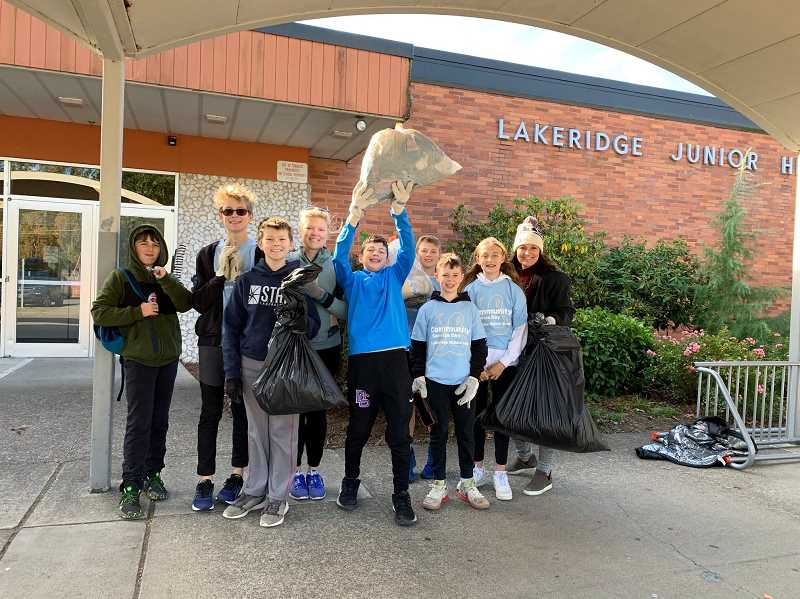 PMG PHOTO: CLAIRE HOLLEY - Lakeridge Middle School sutudents paused their cleanup of the campus to snap a photo.