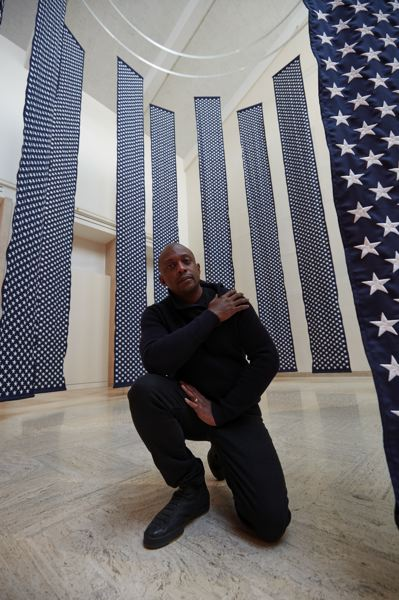 COURTESY PHOTO: PORTLAND ART MUSEUM - Hank Willis Thomas crouches inside his '14,719 (2018)' commissioned installation at Portland Art Museum, which is part of the 'All Things Being Equal ...' exhibit showing through Jan. 12, 2020. The immersive, flag-based sculptural work signifies the number of people killed by gun violence in the United States in 2018.