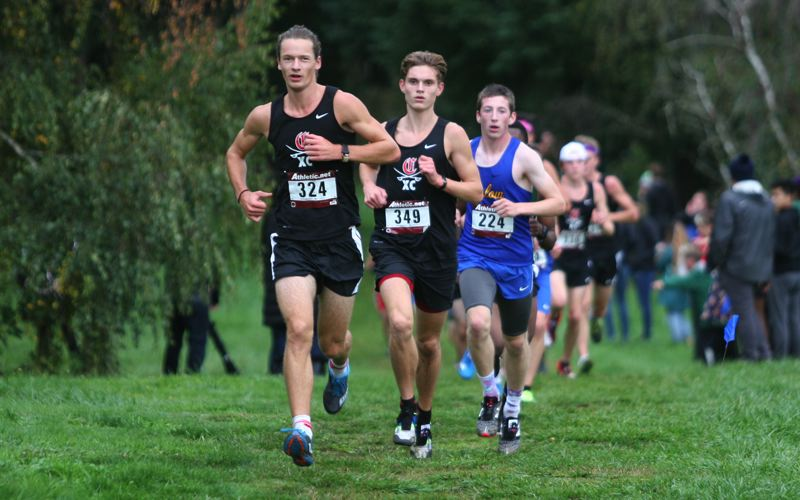 PMG PHOTO: JIM BESEDA - Clackamas' Donovan DeWhitt (324) and Aaron Ruth (349), and Balrow's Braydon Lee help set the pace for the second wave of runners at Wednesday's Mt. Hood Conference cross country meet.