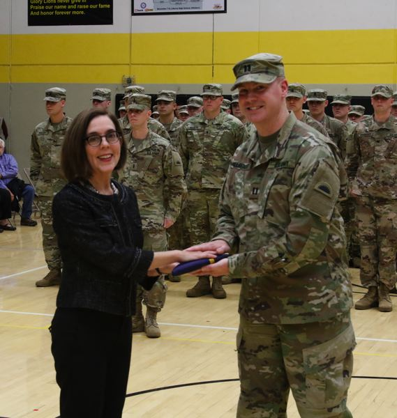 OREGON NATIONAL GUARD PHOTO BY TECH. SGT. AARON PERKINS - Gov. Kate Brown presents the flag to Capt. Jake Allbright, commander, Bravo Company, 741st Brigade Engineer Battalion, during the units mobilization ceremony held at St. Helens High School on Oct. 13.