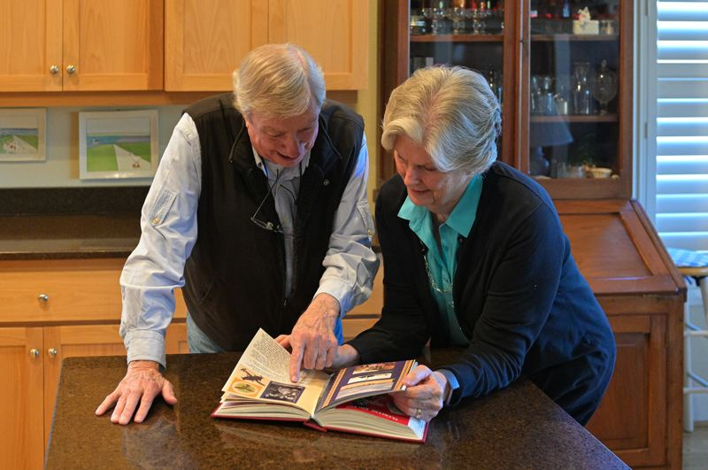 PMG PHOTO: CHRISTOPHER OERTELL - U.S. Air Force veteran Jim Morris and his wife, Diane, look through an album of photos they took while stationed at the Phan Rang Air Base during the Vietnam War.