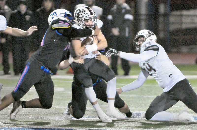 GRAPHIC PHOTO: GARY ALLEN - Newberg's defense faced a formidable Sherwood offense on Friday evening at home in a key Pacific Conference football game.