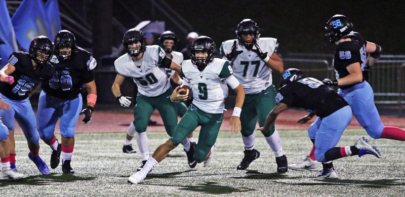 PMG PHOTO: DAN BROOD - Tigard High School junior quarterback Drew Carter (9) finds running room through a hole opened by senior linemen Eric Schulz (50) and Johnny Nomani during the Tigers' 41-14 win at Lakeridge.