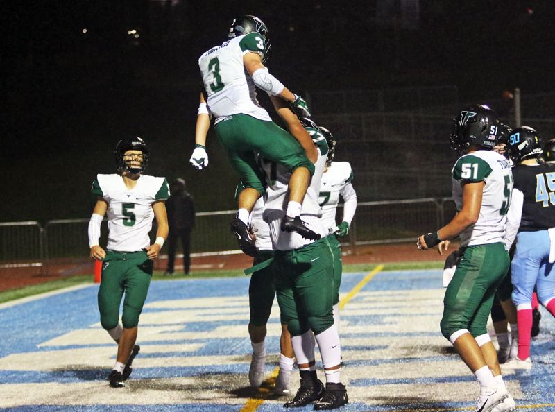 PMG PHOTO: DAN BROOD - Tigard High School senior Hunter Gilbert (3) celebrates with his Tiger teammates after scoring one of his three touchdowns in the team's 41-14 win at Lakeridge on Friday.