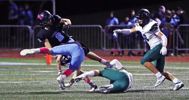 PMG PHOTO: DAN BROOD - Lakeridge High School senior receiver Carson Mike (8) is tripped up after making a 28-yard reception in the second quarter of the Pacers' game with Tigard on Friday.