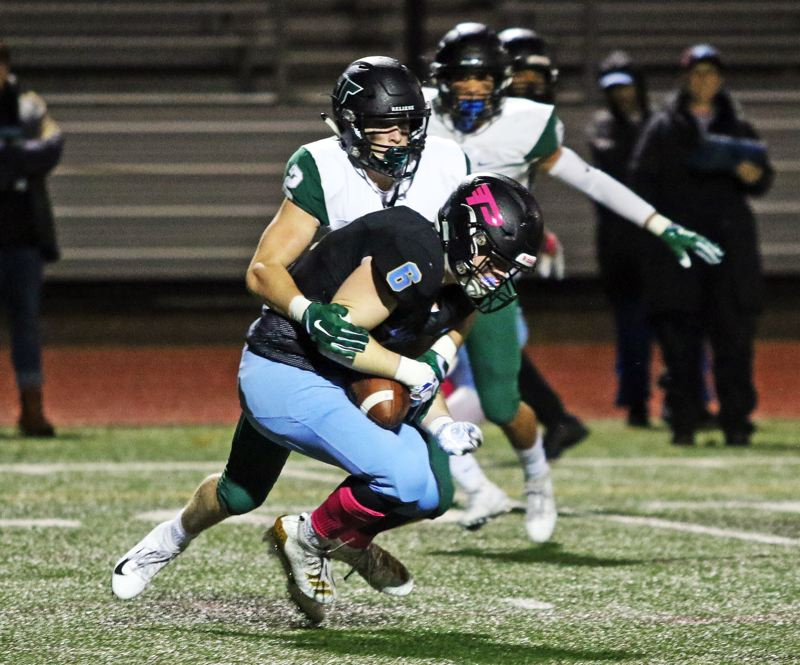 PMG PHOTO: DAN BROOD - Lakeridge High School senior receiver Matt Petersen (6) is tackled by Tigard senior Tyler Penn after making a reception in Friday's Three Rivers League game.