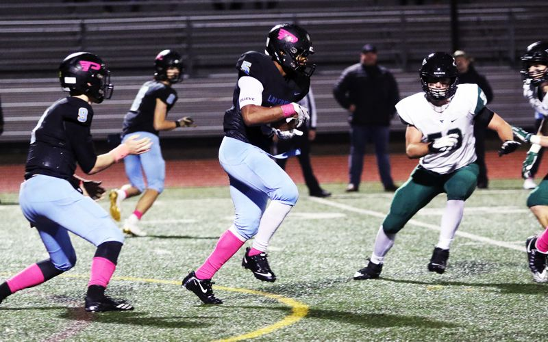 PMG PHOTO: DAN BROOD - Lakeridge High School senior Jalen John (center) looks to gain yardage in Friday's game with Tigard. John rushed for 117 yards on 20 carries in the contest.