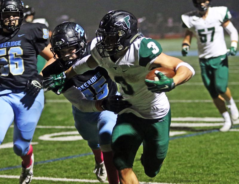 PMG PHOTO: DAN BROOD - Tigard High School senior running back Hunter Gilbert (3) tries to power his way past a Lakeridge defender during Friday's game. Gilbert ran for 197 yards and four touchdowns in the Tigers' 41-14 victory.