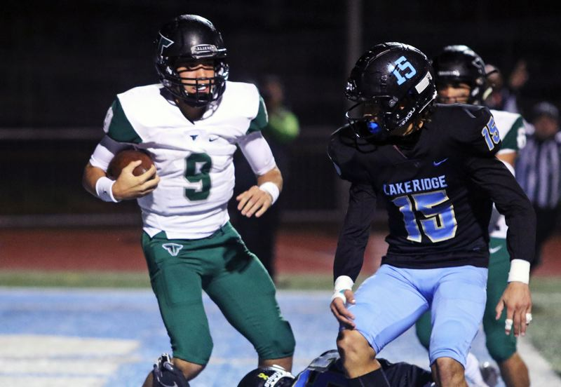 PMG PHOTO: DAN BROOD - Tigard High School junior quarterback Drew Carter (9) gets into the end zone in front of Lakeridge junior Tyeson Thomas during Friday's Three Rivers League game.