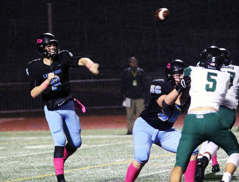 PMG PHOTO: DAN BROOD - Lakeridge High School senior quarterback Cooper Justice (left) fires a pass during Friday's game with Tigard. Justice ran for a touchdown and threw a TD pass in the contest.