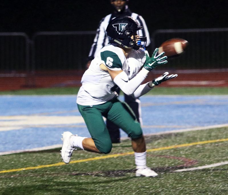 PMG PHOTO: DAN BROOD - Tigard HIgh School senior Max Lenzy grabs the ball to complete a 27-yard touchdown pass play for the Tigers in their 41-14 league win over Lakeridge on Friday.
