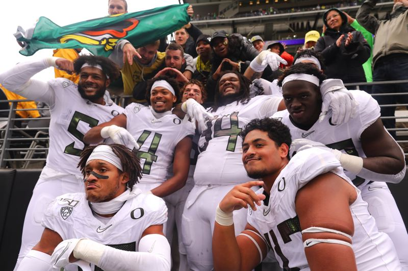 PMG PHOTO: JAIME VALDEZ - Victorious Oregon Ducks pose after defeating Washington on Saturday in Seattle.
