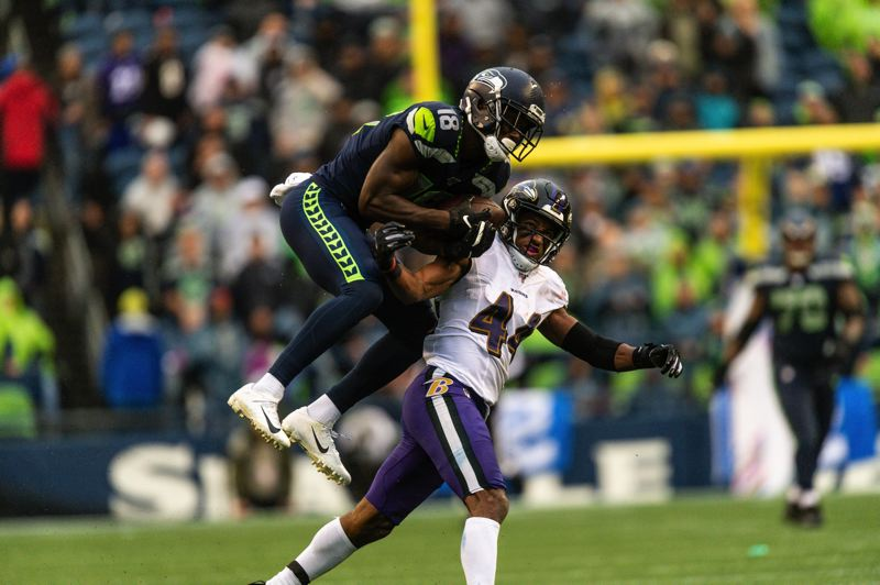 MICHAEL WORKMAN PHOTO - Jaron Brown of Seattle tries to make a leaping catch against Marlon Humphrey of the Baltimore Ravens.