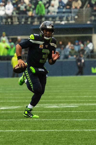 MICHAEL WORKMAN PHOTO - Seattle quarterback Russell Wilson runs to the outside against Baltimore.