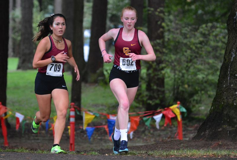 PMG PHOTO: DAVID BALL - Sandys Souvanny Carpenter (789) looks to keep pace with Central Catholics Amare Christensen coming out of a first loop around the park during a league meet at David Douglas on Wednesday.