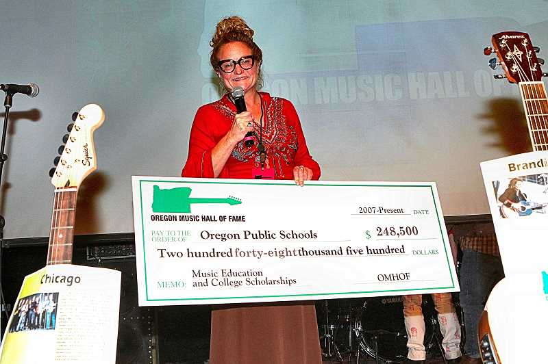 DAVID F. ASHTON - Here, showing a giant check that expresses the cumulative funds Oregon Music Hall of Fame has raised for Oregon school music education, was the nonprofits co-founder, Janeen Rundle.