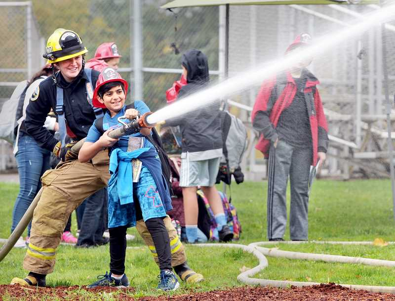 GRAPHIC PHOTO: GARY ALLEN - TVF&R firefighter/EMTs were on hand Friday during Outdoors Field Day to talk to students about fire safety, the department's responsibilities and put the kids in control of a high-pressure hose.