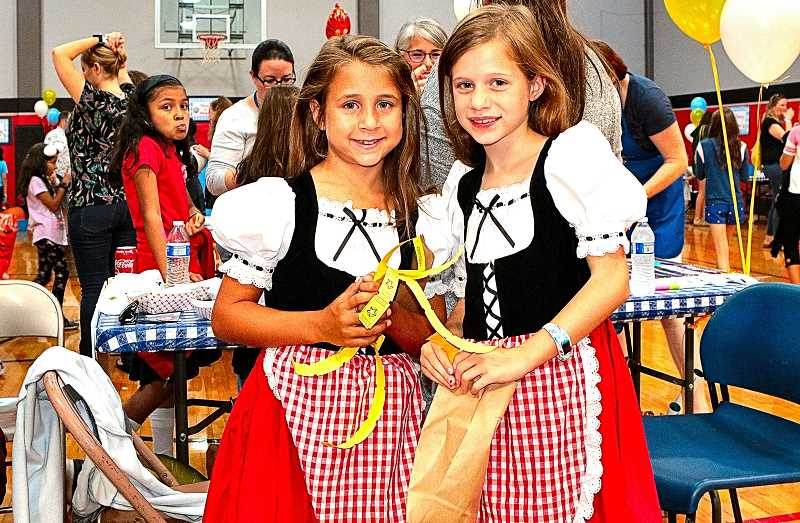 DAVID F. ASHTON - Dressed in derndls to celebrate the Holy Family Oktoberfest were Winterhaven student Lila Chipps, and her friend - Holy Family student Remy McGowan.