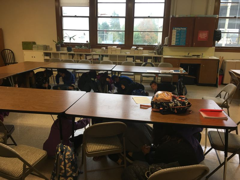 Students at Alliance Charter Academy in Oregon City duck and cover under desks during Clackamas Fire's event to prepare staff, parents and teachers for an earthquake.