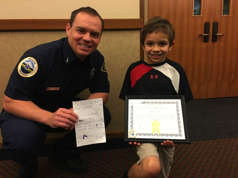 COURTESY PHOTOS: CLACKAMAS FIRE - Clackamas firefighter Brett Glover and Oak Grove resident Michael Terreri, 9, celebrate helping each other save Michael's father's life.