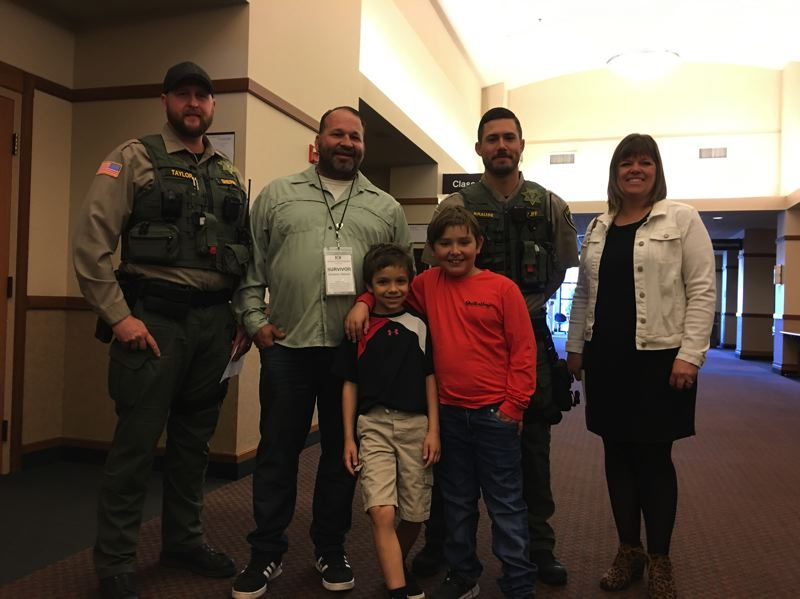 Clackamas County sheriff's deputies Adam Taylor and Scott Krause, who are flanking Oak Grove cardiac arrest survivor Dominic Terreri, supported by members of his family, attend the Oct. 7 event in Oregon City.
