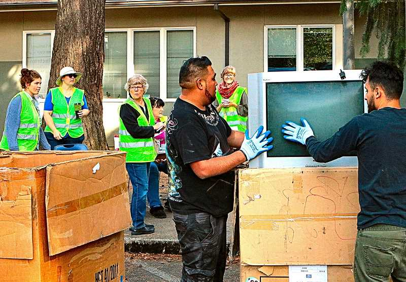 DAVID F. ASHTON - At the September 14th BDNA Electronics Recycling Day, workers lift a weighty and dead old TV into one of the recycling bins.