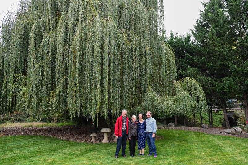PMG PHOTO: CHRISTOPHER OERTELL - Charles and Charline Gebhardt pose for a photo with their daughter, Kim Harrington, and her husband, Scott, underneath a 75 year-old willow tree that is planned to be cut down to make way for a road improvemnt project along Jackson School Road.