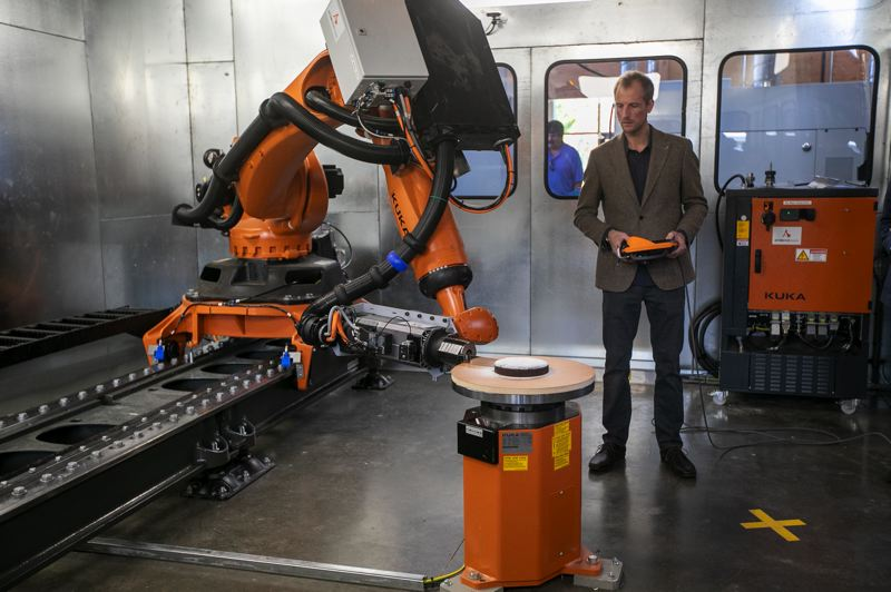 PMG PHOTO: AMANDA LOMAN - Jorn Dettmer, technical manager for the TallWood Design Institute, uses the Kuka robot to cut and serve a slice of cake during the grand opening for the A.A. Red Emmerson Advanced Wood Products Laboratory.