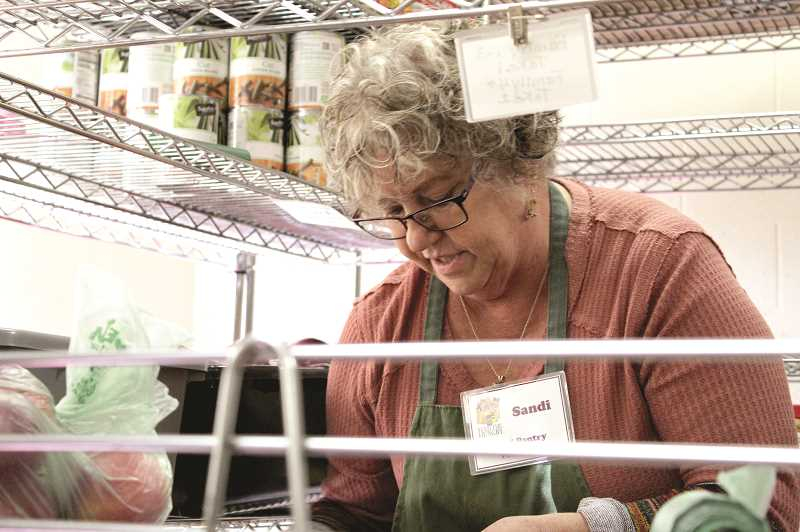 DESIREE BERGSTROM/MADRAS PIONEER - Sandi Okeefe pulls food off of pantry shelves to fill a client's bag. The Madras Community Food Pantry, which operates out of the United Methodist Church, relies on volunteers who help clients shop through the food.